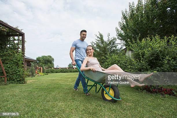 Man pushing girlfriend in wheelbarrow at backyard