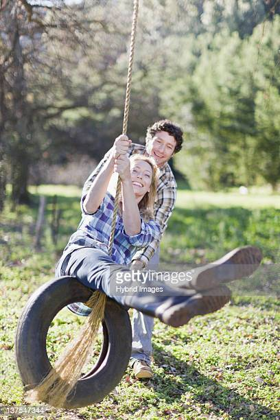 man pushing girlfriend on tire swing - partire bildbanksfoton och bilder