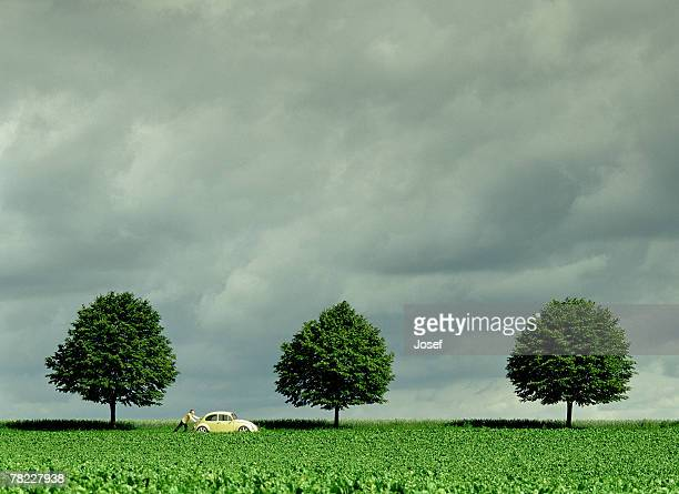 man pushing his car on a country road, grey sky