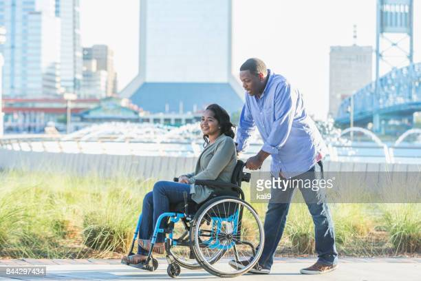 man pushing his teenage daughter in wheelchair - paraplegic stock photos and pictures