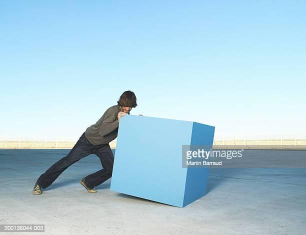 man pushing large block, outdoors - pushing stock pictures, royalty-free photos & images