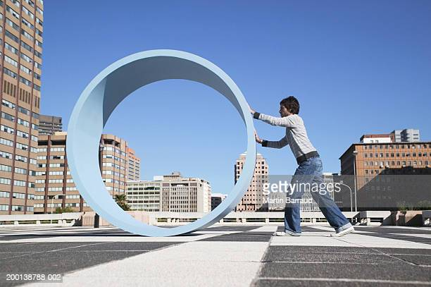 Man pushing large wheel in urban environment