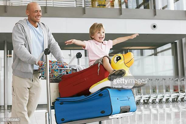 Man pushing little girl riding on baggage cart
