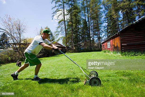 Man pushing manual lawn mower to cut grass
