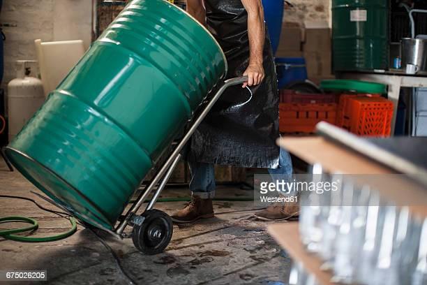 man pushing metal container in a warehouse - empurrar atividade física imagens e fotografias de stock