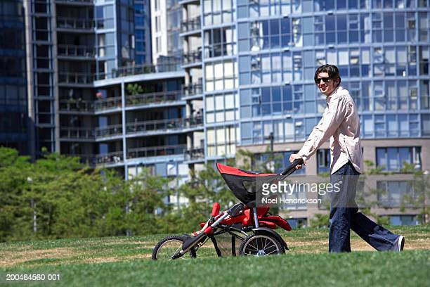 Man pushing pushchair in park, wearing sunglasses