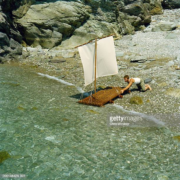 Man pushing raft out to sea, elevated view