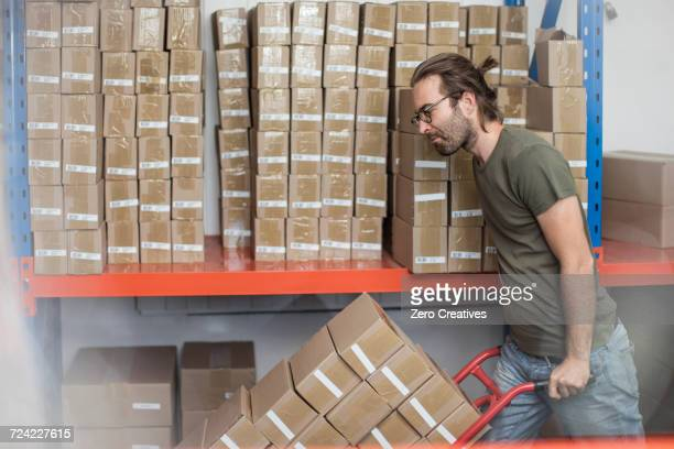 Man pushing sack trolley of stacked cardboard boxes in factory