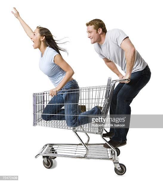 Man pushing shopping cart with girlfriend inside
