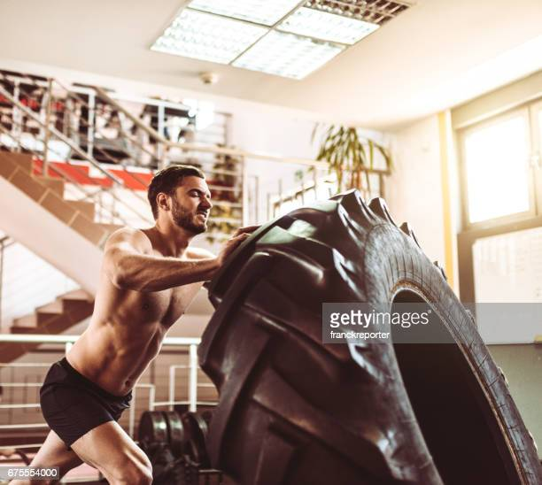 man pushing the truck tire for the cross training