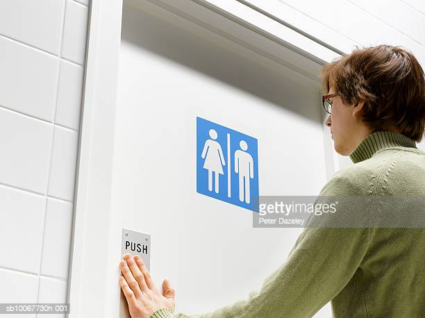 Man pushing toilet door