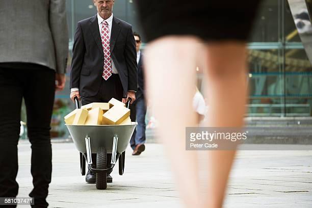 Man pushing wheelbarrow full of gold blocks