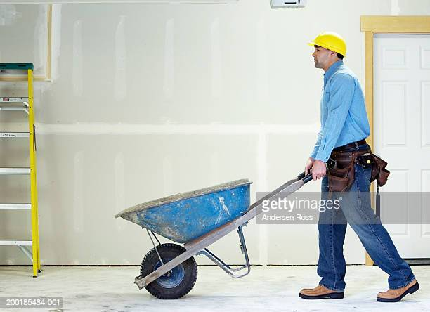 man pushing wheelbarrow on construction site, side view - wheelbarrow stock photos and pictures