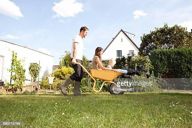 man pushing wheelbarrow with mother and his little son through the garden - eigenheim stock-fotos und bilder