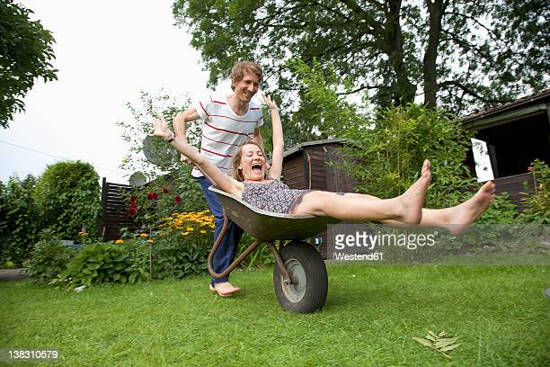 Man pushing wheelbarrow with woman lying on it