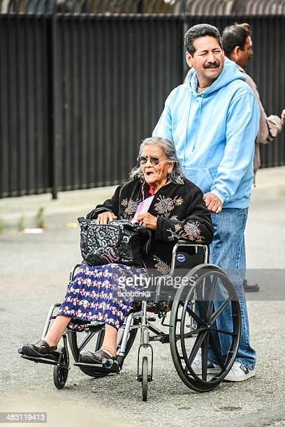 Man pushing wheelchair with disabled senior woman