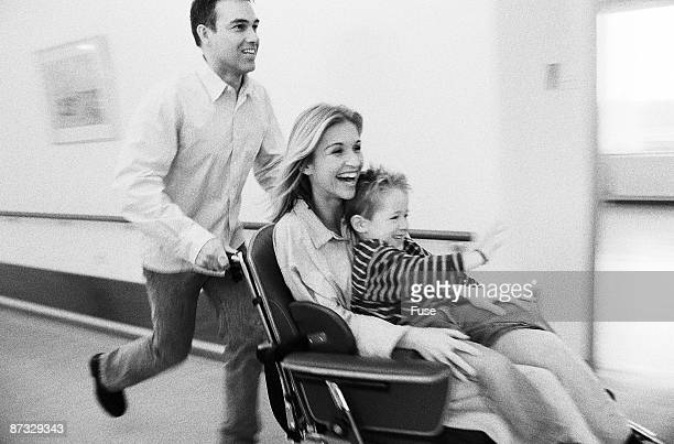 man pushing wheelchair with woman and child - grossesse humour photos et images de collection