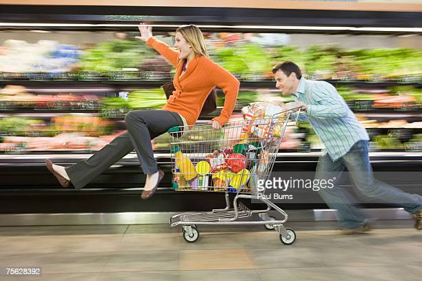 Man pushing woman in supermarket trolley down aisle, blurred motion