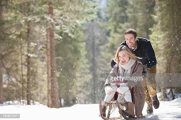 Mann seine Frau auf Schlitten im verschneiten Wald