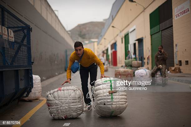 A man pushses some bundles at the El Tarajal border separating Morocco and Spain's North African enclave of Ceuta in Ceuta on October 27 2016 / AFP /...