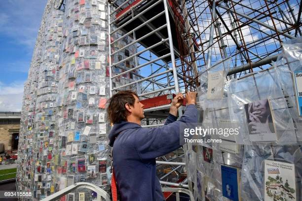 A man put a book on the artwork 'The Parthenon of Books' by the artist Marta Minujin pictured on June 7 2017 in Kassel Germany The documenta 14 is...