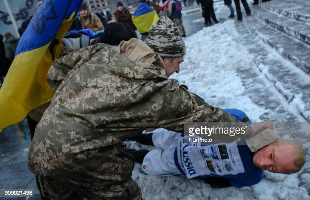A man puts a brick on a face of mannequin depicting Russian President Vladimir Putin dressed in a football uniform during the quotStop Putin Stop...