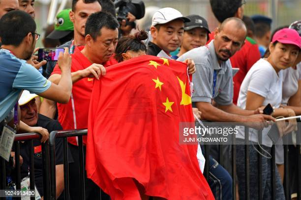 A man puts a Chinese flag around China's Qieyang Shijie after she finished second in the women's 20km walk race competition during the 2018 Asian...