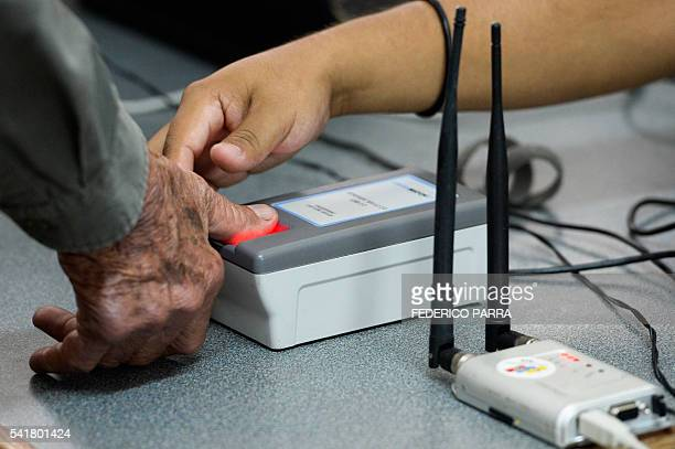 A man puts a finger on a fingerprint scanner during the authentication procedure of his signature for a recall referendum before the National...