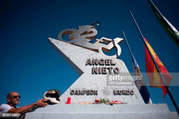 TOPSHOT A man puts a helmet on a tribute monument to Spanish former motorcyclist Angel Nieto during an homage at the Jerez racetrack in Jerez de la...