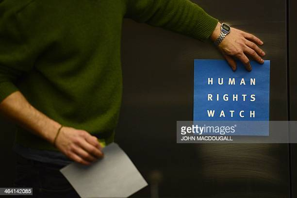 A man puts a logo of USbased rights group Human Rights Watch on the wall as he prepares the room before their press conference to release their...