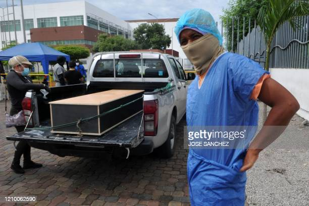 Man puts a protective suit om outside the morgue of the Hospital General Guasmo Sur to enter to identify his relative who died from the coronavirus,...