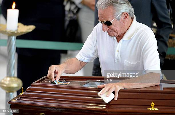 A man puts a sacred image on the coffin of Brazilian architect Oscar Niemeyer during his funeral at Planalto Palace in Brasilia on December 6 2012...