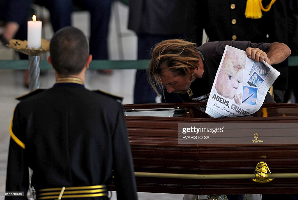 A man puts a sacred image on the coffin of Brazilian architect Oscar Niemeyer during his funeral at Planalto Palace, in Brasilia, on December 6, 2012. Niemeyer, the Brazilian icon who revolutionized modern architecture and designed much of the country's futuristic capital Brasilia, died in Rio de Janeiro Wednesday at 104. The body will return to Rio de Janeiro for another funeral wake followed by the burial, according to Rio de Janeiro's Mayor Eduardo Paes. AFP PHOTO/Evaristo SA