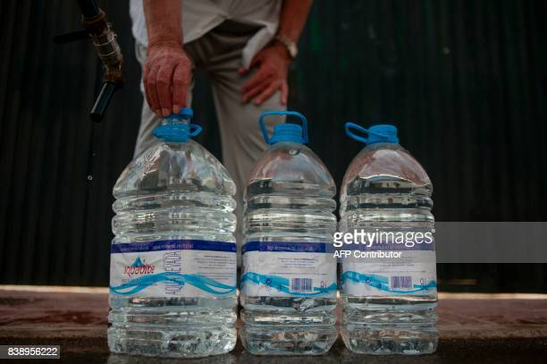 A man puts a tap on a plastic bottle after the distribution of water from a water tanker during a strong drought in Fuente de Piedra on August 25...