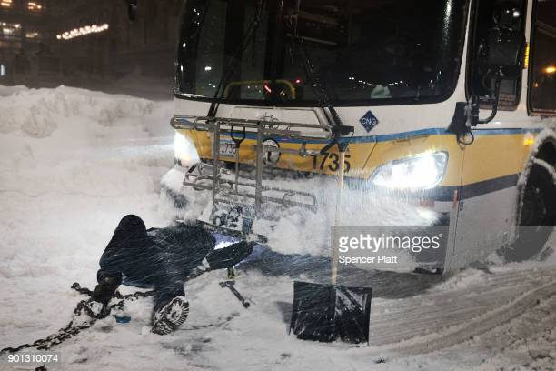 A man puts a tow chain on a city bus that became stuck in the snow in Boston during a massive winter storm on January 4 2018 in Boston United States...