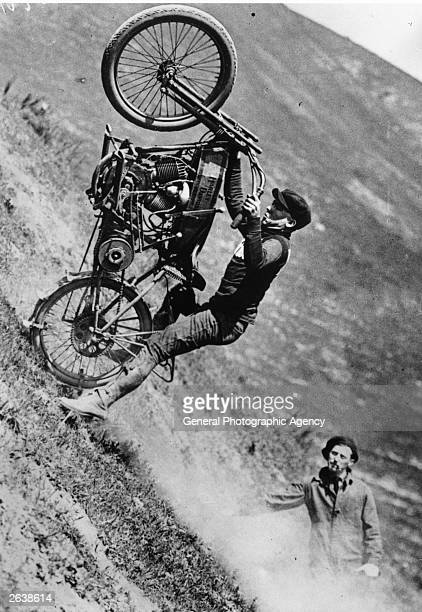 A man puts an early Harley Davidson motorcycle through its paces on a steep gradient
