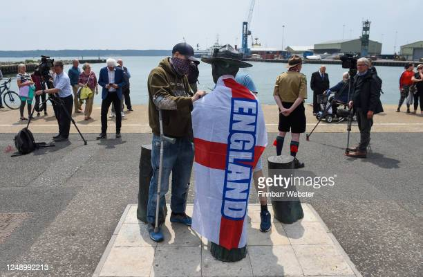 Man puts an England flag on the Lord Baden-Powell statue on June 11, 2020 in Poole, United Kingdom. The statue of Robert Baden-Powell on Poole Quay...