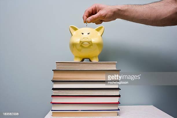 Man puts coin in piggy bank Saving Money for School