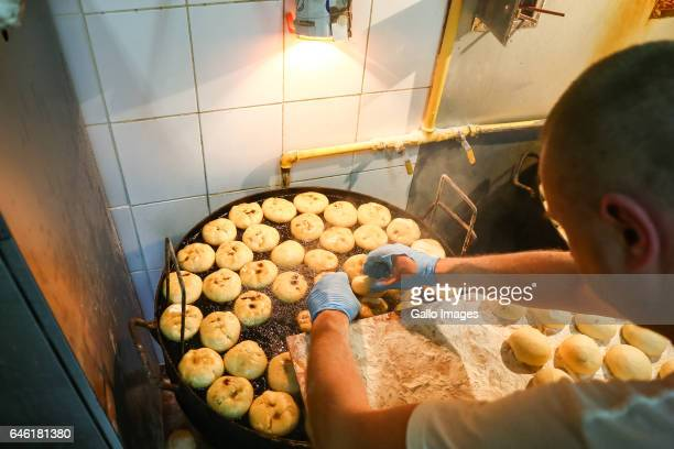 A man puts donuts on a large frying pan during Fat Thursday on February 23 in Warsaw Poland Fat Thursday is a traditional Catholic Christian feast...
