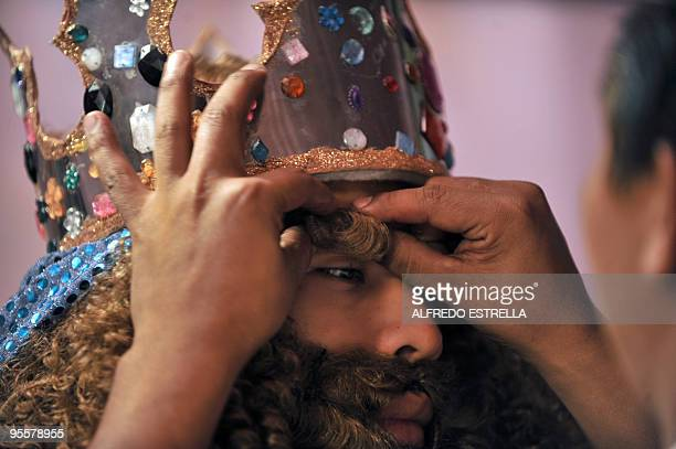 A man puts false eyelashes on 'Melchoir' during the preparation of the Three Wise Men in Mexico City's Guerrero neighbourhood before a walk around...
