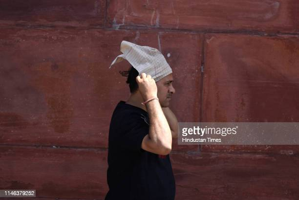 A man puts handkerchief on his head to protect himself from the scorching sun on a hot day at Raisina Hills on May 26 2019 in New Delhi India During...