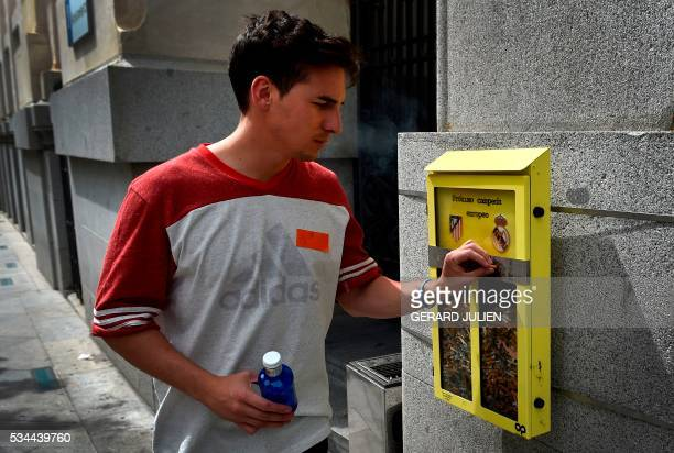 A man puts his cigarette butt in an ashtray displayed by the City Council and shaped as a ballot box inviting the passerby to vote with their...