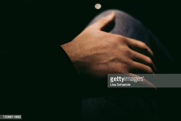 man puts his hand on a woman's thigh by night - sexual abuse stock pictures, royalty-free photos & images
