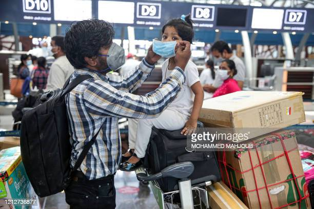 Man puts on a mask on the face of a young girl as they wait with their luggage at the check-in counter along with other Indian nationals residing in...