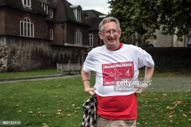 A man puts on a Tshirt with a logo of support for workers from the Bombardier factory in Belfast as workers and supporters meet MPs to urge for...