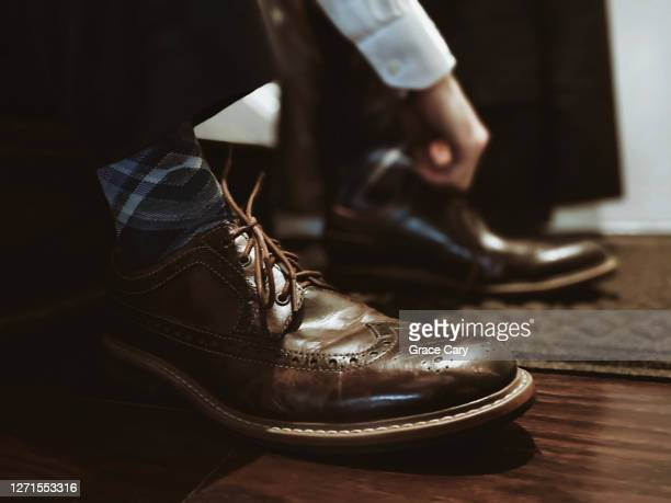 man puts on dress shoes - brown shoe stock pictures, royalty-free photos & images