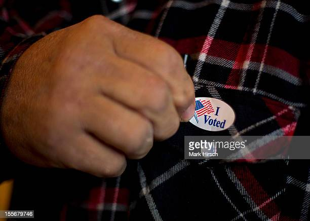 A man puts on his I Voted sticker after voting at a polling station on November 6 2012 in Otter Creek Iowa US citizens go to the polls today to vote...