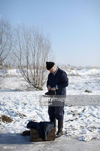 A man puts on his iceskates as he prepares to skate on a frozen fen in subzero temperatures on February 11 2012 in Sutton England Last night the Met...
