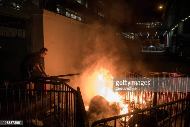A man puts out a fire burning in a makeshift barricade as police and protesters clash after an antiextradition bill march on July 21 2019 in Hong...