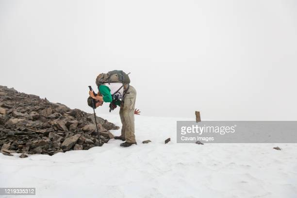 man puts rocks on snow for navigation, kenai peninsula, alaska - kenai mountains stock pictures, royalty-free photos & images
